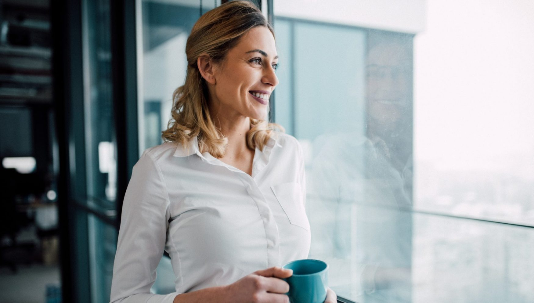 Young business woman looking through the office window with cup of coffee.